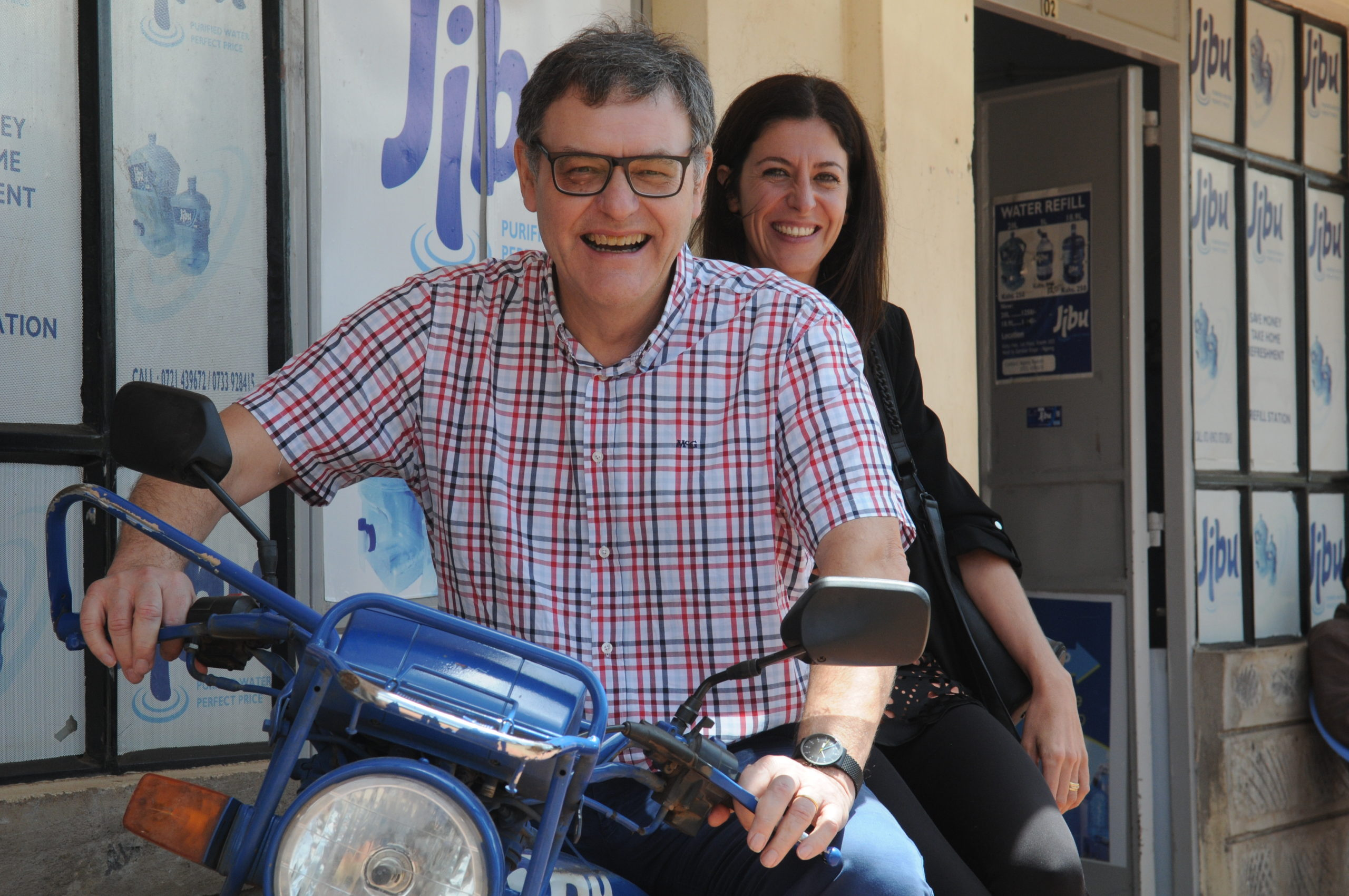 Incofin Founder with Regional Director and Impact Manager Dina Pons on a motorbike that brings clean drinking water from a water kiosk to local vendors.